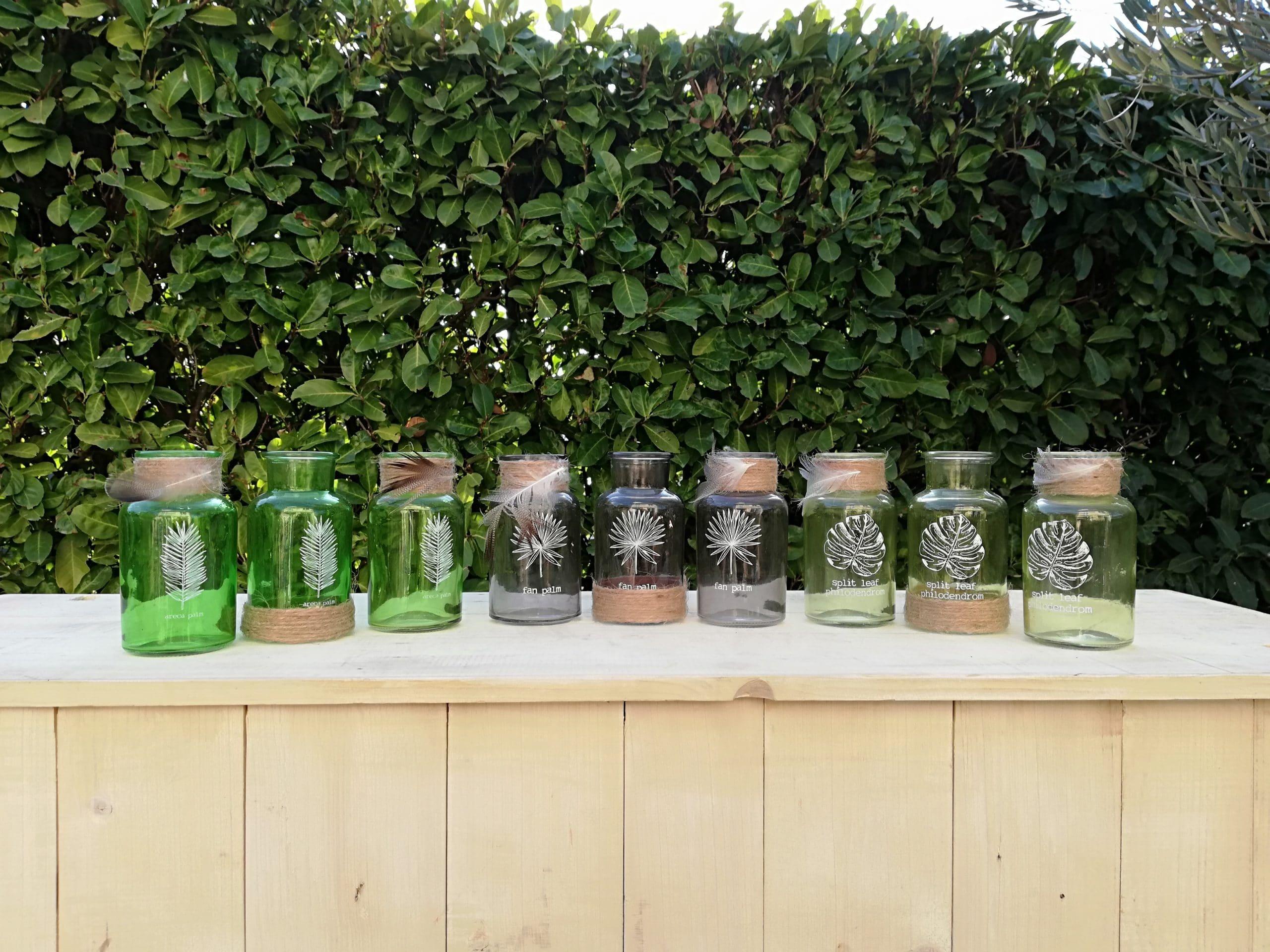 location de petites bouteilles en verres de différentes couleurs pour la décoration de votre mariage champêtre proposées par esprit pop'up